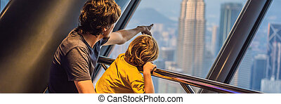 Dad and son are looking at Kuala lumpur cityscape. Panoramic view of Kuala Lumpur city skyline evening at sunset skyscrapers building in Malaysia. Traveling with kids concept BANNER, LONG FORMAT