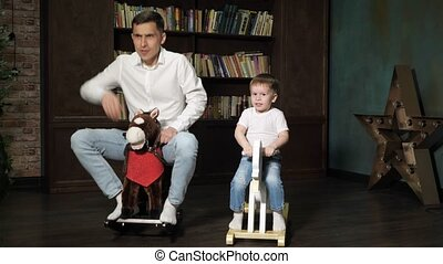 Dad and son are playing together riding on toy horses...