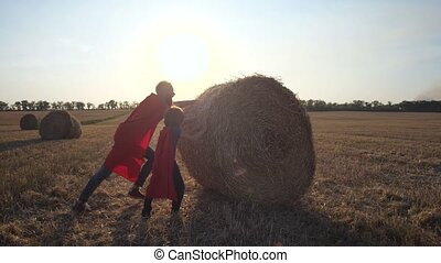 Dad and son as strong heroes rolling straw stack