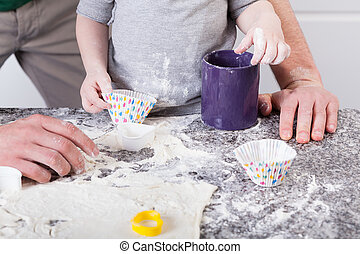 Dad and son baking cookies