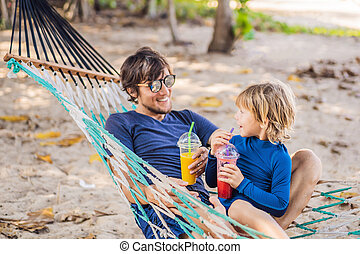 Dad and son having fun in a hammock with a drinks