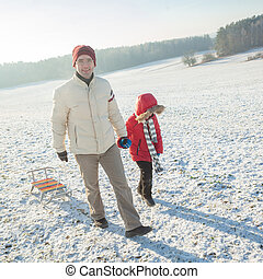 Dad and son having fun in the winter. Dad and son walking in winter on the background of the sun. concept of the relationship between father and son