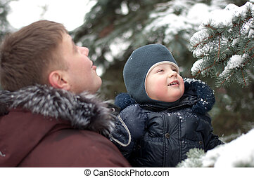 Dad and son on a walk in the woods in winter