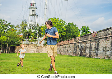 Dad and son on background of Fort Cornwallis in Georgetown, Penang, is a star fort built by the British East India Company in the late 18th century, it is the largest standing fort in Malaysia. Traveling with children concept