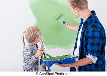Dad and son painting wall in child's room