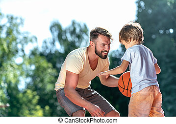 Dad and son playing basketball