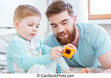 Dad and son playing with toys on bed