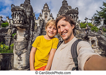 Dad and son tourists on background of Three stone ladders in...