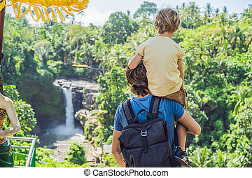 Dad and son tourists on the background of a waterfall. Traveling with kids concept. What to do with children Children friendly place
