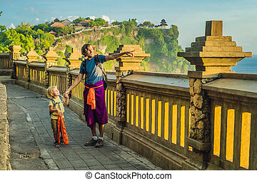 Dad and son travelers in Pura Luhur Uluwatu temple, Bali, Indonesia. Amazing landscape - cliff with blue sky and sea. Traveling with kids concept