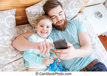 Dad and son using cell phone on bed together