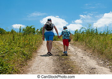 Dad and son walking along the road