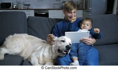 Dad and son with dog watching cartoons on touchpad - Caring...