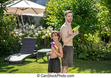 Dad and son with water pistols getting ready to play
