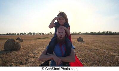 Dad carrying son on shoulders walking across field
