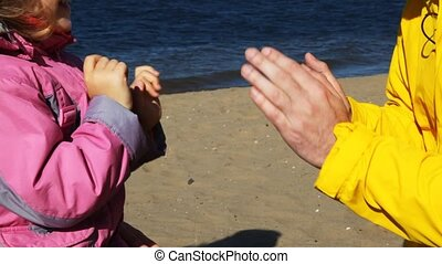 dad, daughter and mum play together in palms on river beach