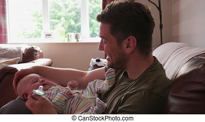 Dad Entertaining His Baby Boy - Dad and newborn baby...