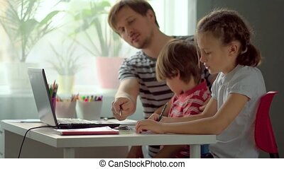 Dad explains son and daughter homework using a digital tablet laptop.