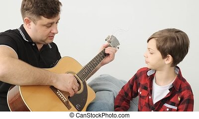 Dad explains to his son how to play guirat slowly front view...