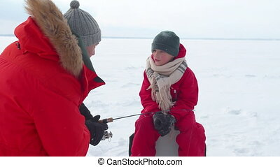 Dad and son fish together in winter