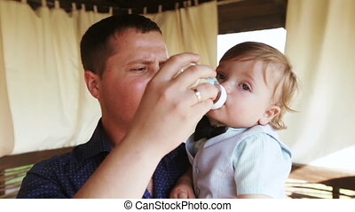 Dad feeding baby with bottle