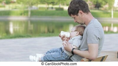 On the bank of the city pond dad with a baby in his arms feeds milk from a bottle