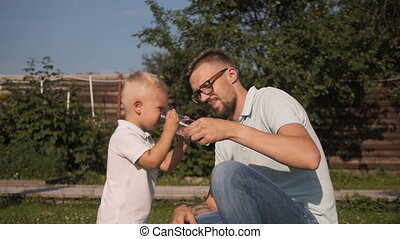 Dad Giving Drinking Water To His Son In Garden. Little Boy Drinking Water