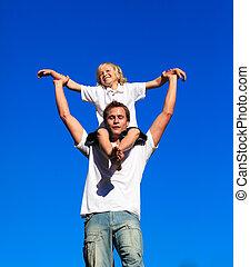 Dad giving his son a piggyback ride