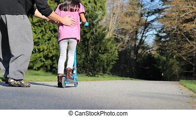 Dad Helps Daughter Ride Scooter - A nervous dad helps his...