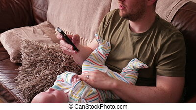 Dad Holding Baby While on his phone