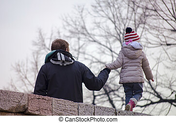 Dad holding his daughter by the hand outdoors