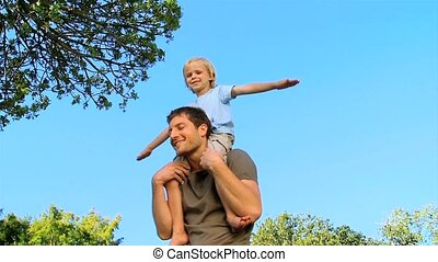 Dad holding his son on shoulders