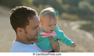 Dad holding on hands his baby daughter near the lake