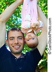 Dad holds the baby upside down outdoor.
