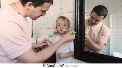 Dad is brushing teeth decay to his son bathroom morning