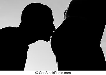 Dad kissing a pregnant belly in backlight