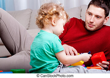 Dad looks at his son playing with blocks