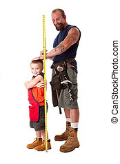 Dad measuring height of son - Father wearing tool belt with...