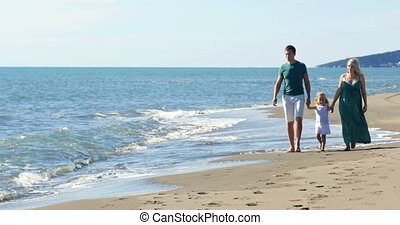 Dad mom and daughter walk along the beach
