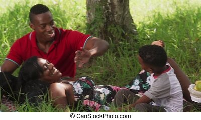 Happy black couple with son in city park. African american family with young man, woman and child eating snack during picnic. Recreation for husband, wife and boy. Slow motion