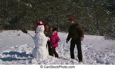 Dad, mother and little daughter make a snowman in the meadow near the forest.