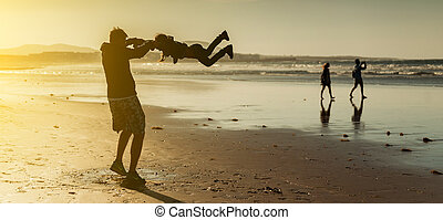Dad playing with his daughter on the beach