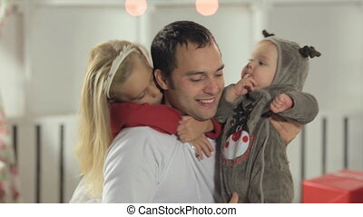 Dad having fun with his little daughter with long hair and baby dressed as deer in New Year atmosphere