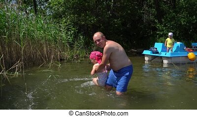 Dad plays with daughter in water. Son standing on catamaran....