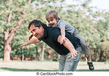dad plays with his little son on a walk in the Park .