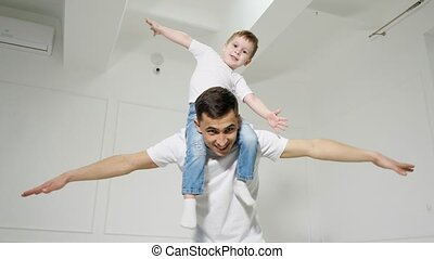 Dad plays with son sitted on his shoulders, they spread their arms out to the sides depicting a plane.