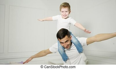 Dad plays with son sitted on his shoulders, they spread their arms out to the sides depicting a plane, close-up