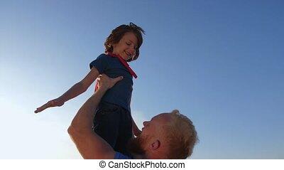 Dad raising son high imitating superhero's flight - Close-up...