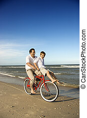 Dad riding red bicycle with son on handlebars. - Caucasian...