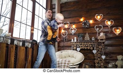 Dad shakes his son at the window on the background of the Christmas fireplac